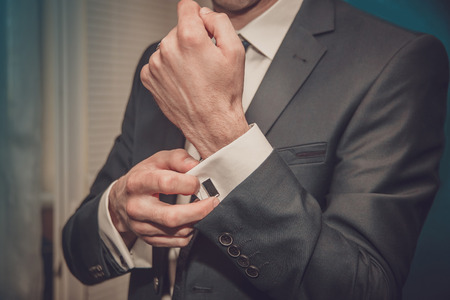 Photo pour groom putting on cuff-links as he gets dressed in formal wear close up - image libre de droit
