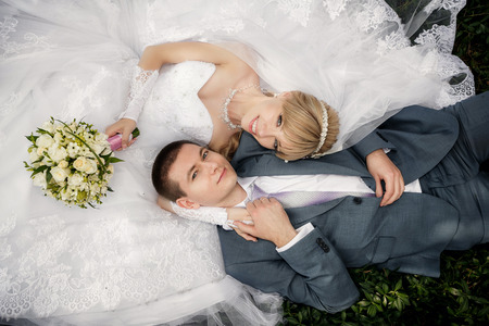 Photo for Happy bride and groom are lying on green grass - Royalty Free Image
