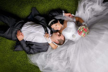 Photo pour Smiling bride and groom lying on the grass-like carpet. - image libre de droit