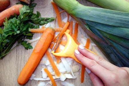 Foto de Organic vegetables peeling in the kitchen - Imagen libre de derechos