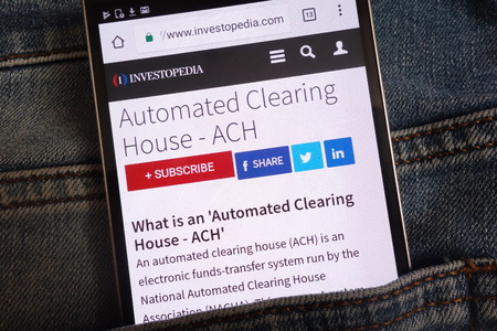 Foto de KONSKIE, POLAND - JUNE 11, 2018: An article about automated clearing house (ACH) on Investopedia website displayed on smartphone hidden in jeans pocket - Imagen libre de derechos