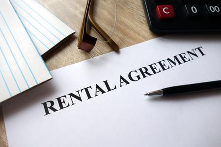 Photo pour Rental agreement form with pen, calculator and glasses on desk - image libre de droit