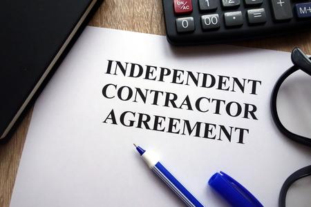 Foto de Independent contractor agreement, pen, glasses and calculator on desk - Imagen libre de derechos