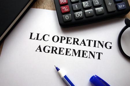 Photo pour LLC operating agreement, pen, glasses and calculator on desk - image libre de droit