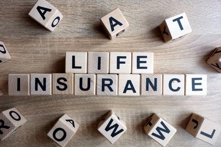 Photo pour Life insurance text from wooden blocks on desk - image libre de droit