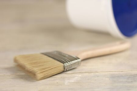 Photo for A paint brush is next to a plastic paint bucket with a blue lid on an old white vintage wooden board. Brick wall in the background. - Royalty Free Image