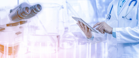 Foto de Medical science research and development concept - Doctor holding tablet computer with scientific instrument, microscope and  chemical test tube in lab background. - Imagen libre de derechos