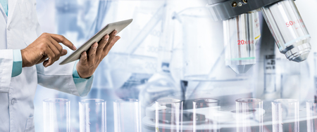 Foto de Science research and technology concept - Scientist holding tablet computer with scientific instrument, microscope and chemical test tube in lab background. - Imagen libre de derechos