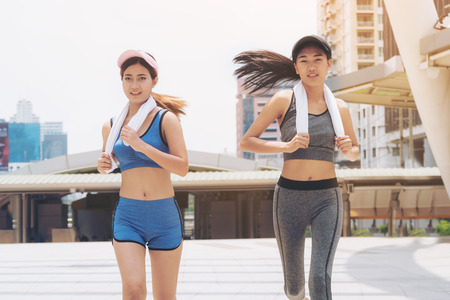 Photo pour Two healthy woman running in the city background. Concept of women fitness, healthy urban lifestyle and urban running. - image libre de droit