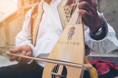 Photo for A busker plays traditional Croatian folk music with a 3-string instrument (lijerica) in the old city of Dubrovnik, Croatia. - Royalty Free Image