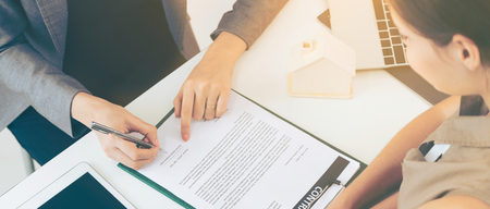 Photo pour Client signs document regarding real estate activity next to lawyer or real estate agent sitting at office desk. Business concept of selling and buying house. - image libre de droit