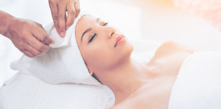Photo pour Relaxed young woman lying on spa bed prepared for facial treatment and massage in luxury spa resort. Wellness, stress relief and rejuvenation concept. - image libre de droit