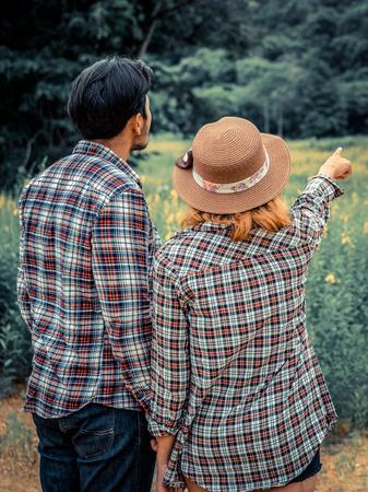 Foto de Happy couple take a romantic walk in green grass field on the hills. Travel and honeymoon concept. - Imagen libre de derechos