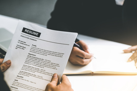 Photo for Human resources department manager reads CV resume document of an employee candidate at interview room. - Royalty Free Image