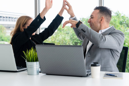 Photo for Success business partner - Businesswoman and businessman celebrating together in modern workplace office. People corporate teamwork concept. - Royalty Free Image