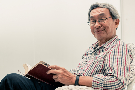 Photo pour Happy senior Asian man reading book on the chair in living room at home. Retirement lifestyle and aging society concept. - image libre de droit