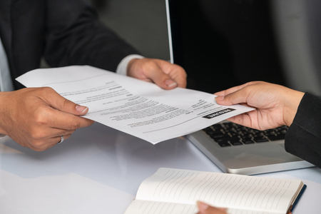 Photo for Close up view of employee candidate hands CV resume document to the interviewer HR human resources department manager at the interview room. Job application, recruit and labor hiring concept. - Royalty Free Image