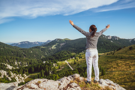 Foto de Young woman traveler and explorer travels in the forest and mountain nature landscape hiking across Zavizan Gora in Croatia. - Imagen libre de derechos
