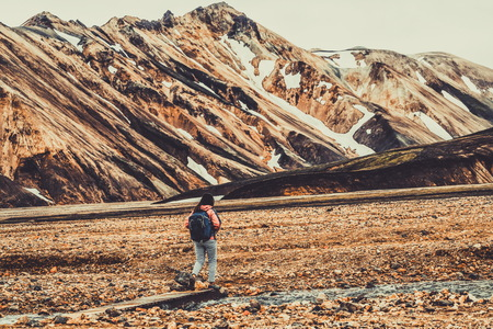 Foto de Traveler hiking at Landmannalaugar surreal nature landscape in highland of Iceland, Nordic, Europe. Beautiful colorful snow mountain terrain famous for summer trekking adventure and outdoor walking. - Imagen libre de derechos