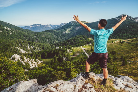 Foto de Young man traveler and explorer travels in the forest and mountain nature landscape hiking across Zavizan Gora in Croatia. - Imagen libre de derechos