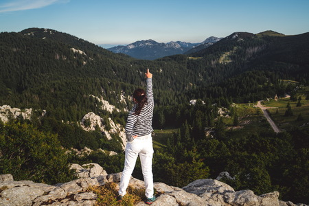 Foto de Young woman traveler and explorer travels in the forest and mountain nature landscape hiking across Zavizan Gora in Croatia. - Imagen libre de derechos
