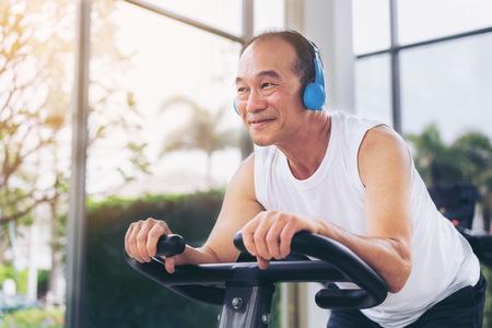 Photo pour Senior man exercise on cycling machine in fitness center. Mature healthy lifestyle. - image libre de droit