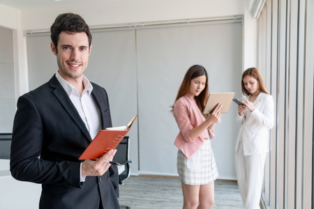 Foto de Happy young handsome businessman reading book and working in office with colleagues and friend at workplace. Corporate business people group. - Imagen libre de derechos
