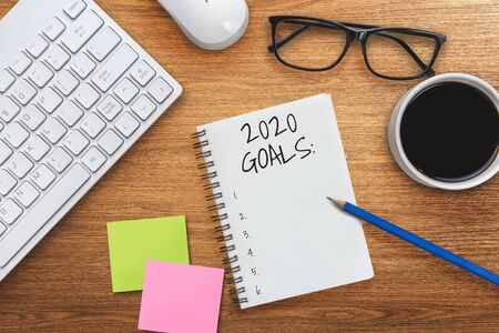 Foto de New Year Resolution Goal List 2020 - Business office desk with notebook written in handwriting about plan listing of new year goals and resolutions setting. Change and determination concept. - Imagen libre de derechos