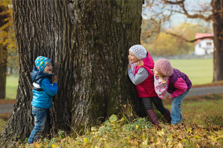 Photo for Portrait little children as they play hide and seek in the park - Royalty Free Image