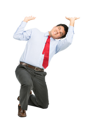 Foto de A stressed latino businessman in business clothes on knee using arms pushing up, resisting against crushing imaginary weight, object under heavy stress, feeling pressure. Isolated on white background - Imagen libre de derechos