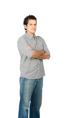 Photo for Profile of critical, judgmental hispanic man in casual clothes with arms crossed looking at camera expressing stoic, harsh, unhappy, disappointed attitude. Vertical - Royalty Free Image