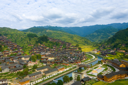 Photo for High angle view of the river and mountains behind the traditional wooden houses of Xijiang Miao ethnic minority village in Guizhou, China - Royalty Free Image