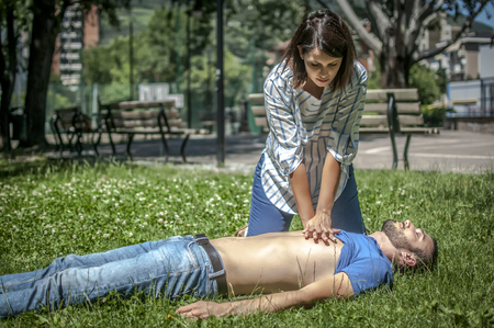 Foto de Girl making cardiopulmonary resuscitation to an unconscious guy after heart attack - Imagen libre de derechos