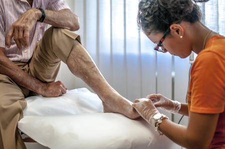 Foto de podiatry doctor curing an elderly patient foot - Imagen libre de derechos