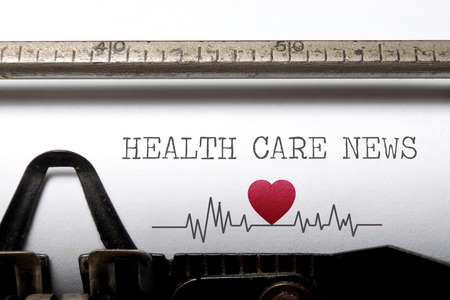 Photo pour Health care news printed on an old typewriter with heart beat pulse sketch - image libre de droit