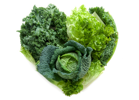 Foto de Green healthy vegetables in the shape of a heart isolated over a white background - Imagen libre de derechos