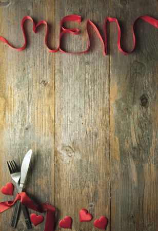 Foto de Valentine menu background made from red ribbon bow with cutlery and baubles - Imagen libre de derechos