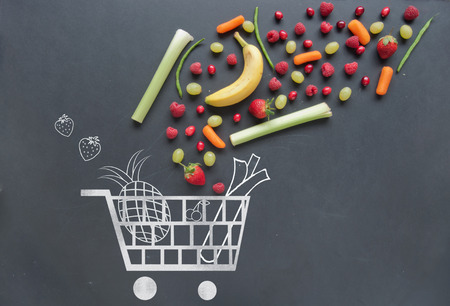 Photo pour Grocery shopping cart sketched on a chalkboard combined with fruits and vegetables - image libre de droit