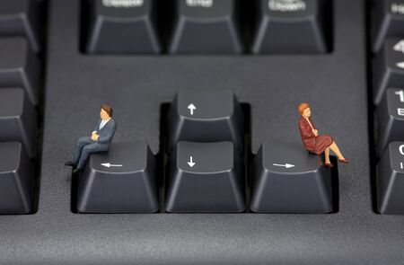 Concept image depicting a divorce or a relationship break-up. Two miniature figures are sitting on a computer keyboard in opposing directions.