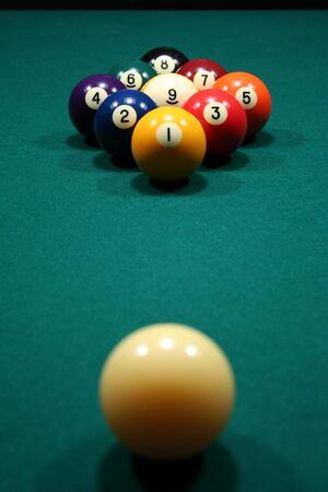 9-Ball rack of billiard balls on a green felt pool table.