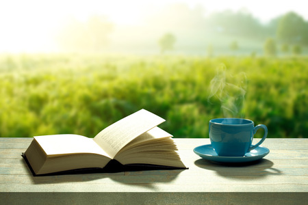 Photo pour Open book with a coffee cup and a wooden table - image libre de droit