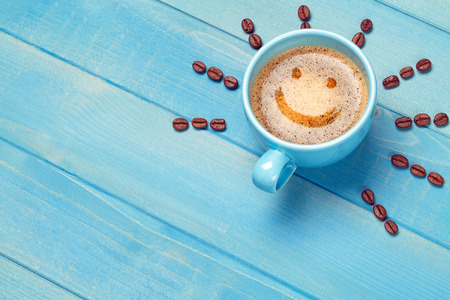 Foto de Coffee cup with smiley face on blue wooden table - Imagen libre de derechos