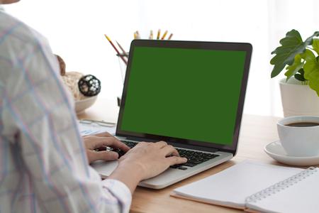 Foto de Over the shoulder shot of a woman typing on a computer laptop with a key-green screen. Woman hand typing laptop with green screen. - Imagen libre de derechos