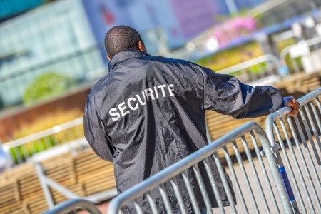 Foto de Security worker leaning over metallic fence and watching over the construction area - Imagen libre de derechos