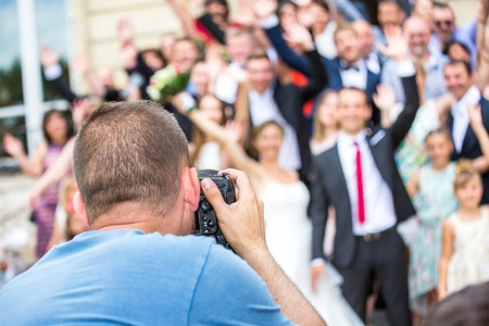 Photo pour Wedding photographer in action, taking a picture of group of guests - image libre de droit