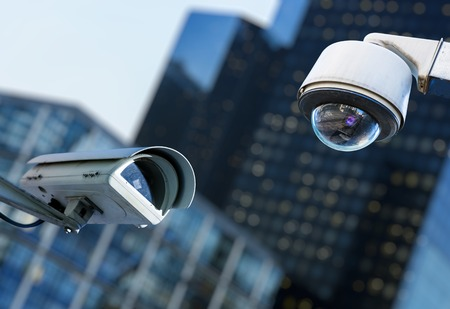 Photo for two cctv security camera in a city with blury business building on background - Royalty Free Image