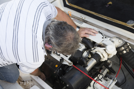 Foto de close-up of a man repairing a boat engine under sunny day - Imagen libre de derechos