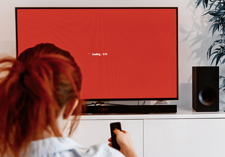 Foto de Redhead woman sitting in her living room and holding a TV remote control in front of a screen waiting message while loading an application on her connected TV - Imagen libre de derechos