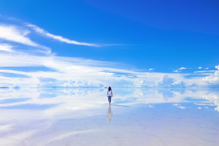 Photo for Female walks into the horizon at Salar de Uyuni, the Salt Flats in Bolivia - Royalty Free Image