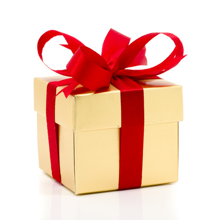 Foto de Beautiful gold present box with red bow and ribbons on white backgound - Imagen libre de derechos